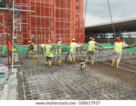 SELANGOR, MALAYSIA -JULY 13,2016: A group of construction workers pouring raw concrete using concrete pump hose into the floor slab form work at the construction site.