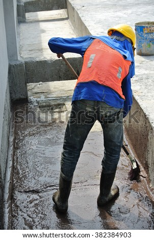 SELANGOR, MALAYSIA - SEPTEMBER 12, 2014: A construction worker apply layer of bituminous waterproofing at the building roof slab surface.