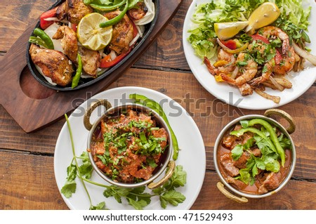 Selection of curry dishes with meat and prawns on wooden background