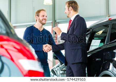Seller or car salesman and customer in auto dealership, they shaking hands, hands over the car keys and seal the purchase of the auto or new car