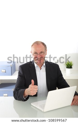 Senior businessman giving thumbs up gesture Senior businessman seated at his desk with his laptop giving a thumbs up gesture of agreement