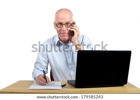 Senior businessman in office with a phone