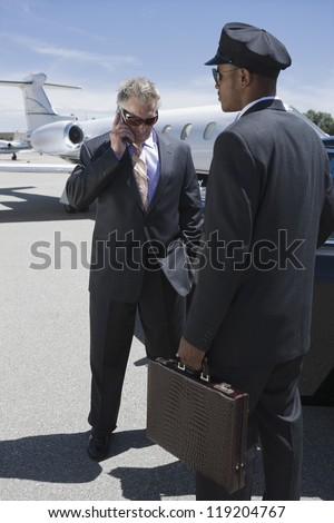 Senior businessman standing outside private jet and talking on phone