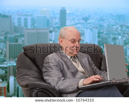Senior businessman working on his laptop in front of the office window in a big city.
