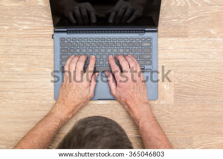 Senior caucasian adult man typing on laptop keyboard on wooden desk in photo taken from above
