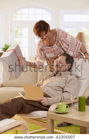 Senior couple celebrating birthday. Wife giving present to her husband, resting in armchair.?