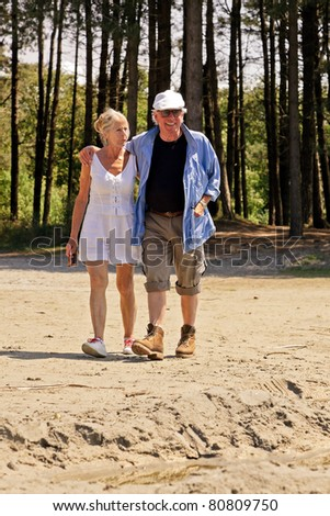Senior couple embraced walking in nature.