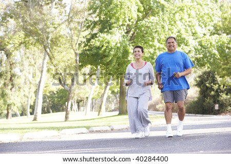 Senior Couple Jogging In Park