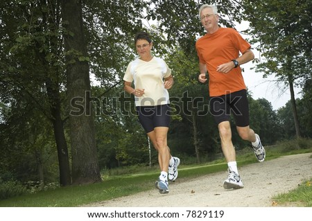 Senior couple running through the woods.