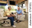 Senior couple sitting in RV holding coffee cups and smiling. - stock photo