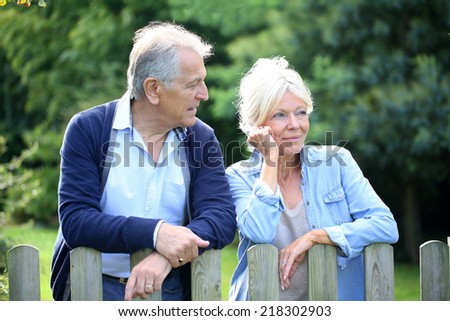 Senior couple standing by fence in yard