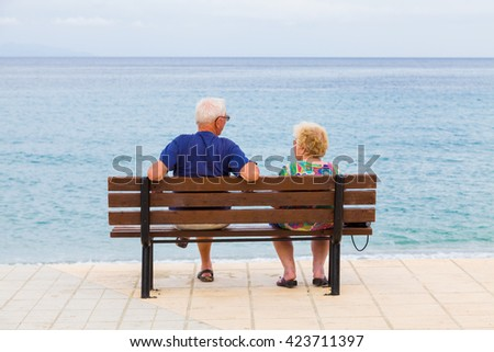 Senior couple talking at the beach in a cloudy day at the shores of the Ionian see in Kefalonia island, Greece.