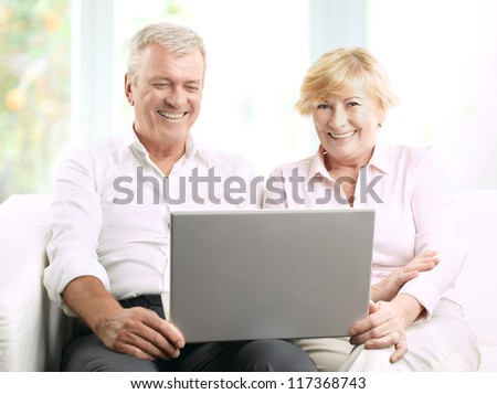 Senior couple using a laptop at home