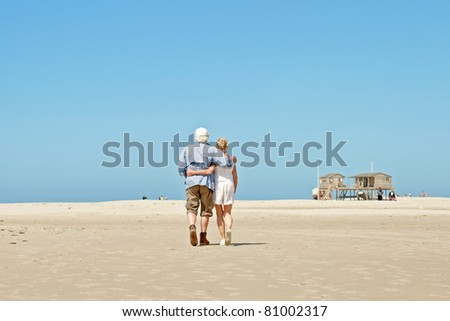 Senior couple walking on empty beach under clear blue sky on hot summer day.