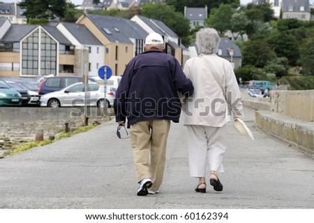 Senior couple walking together holding their hands.