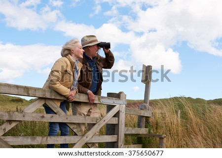 Senior Couple With Binoculars Walking In Countryside