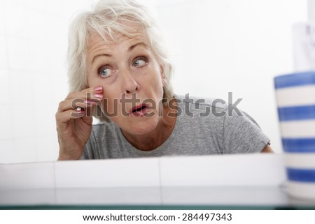 Senior Couple Woman Looking At Reflection In Mirror For Signs Of Ageing
