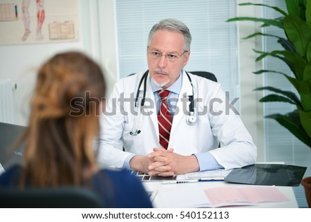 Senior doctor listening to a patient in his studio