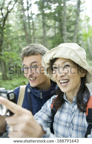 senior husband and wife holding camera in greenery