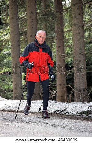 Senior in winter on snow when Nordic walking