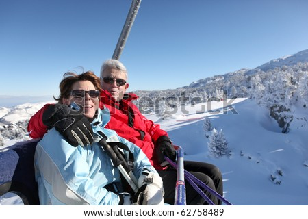 Senior man and senior woman sitting on a chairlift