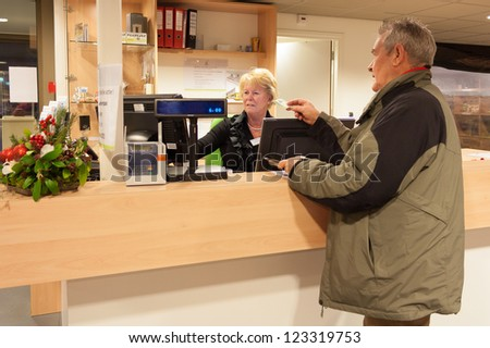 Senior man purchasing museum pass at front desk operated by a senior female volunteer cashier