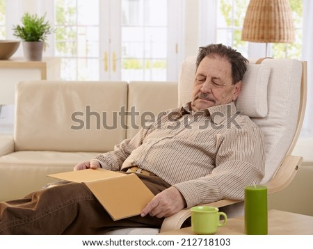Senior man sleeping in armchair at home.