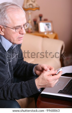 Senior man using a memory stick and a laptop