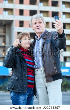 Senior people making selfie standing together with house key