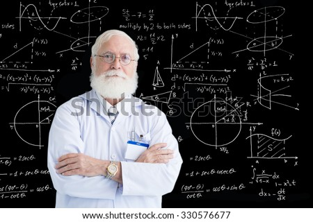 Senior scientist standing at blackboard covered with his graphs and formulas