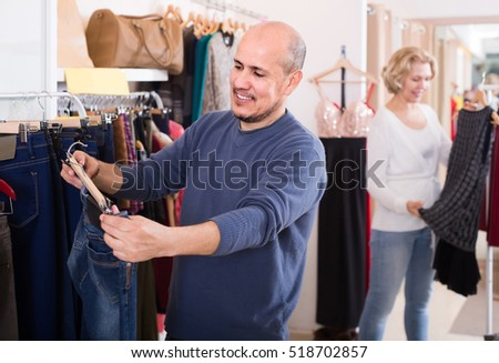 senior spanish spouses buying pair of classic jeans in boutique
