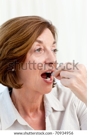 Senior taking pills at home