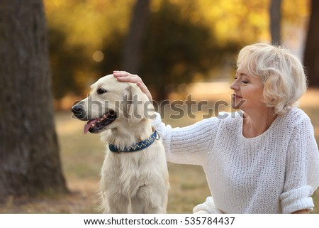 Senior woman and big dog sitting on grass in park