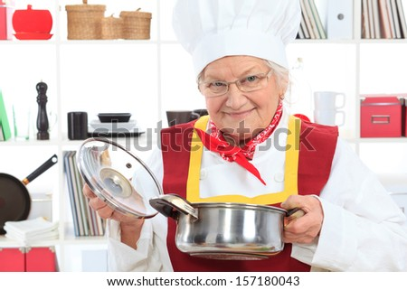 Senior woman chef cooks in the kitchen.