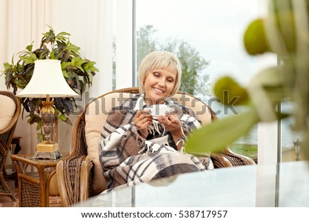 Senior woman drinking tea wrapped in plaid
