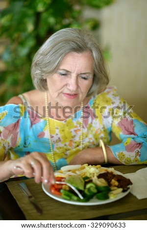 Senior woman eating breakfast at a cafe
