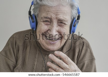 senior woman listening music with blue headphones