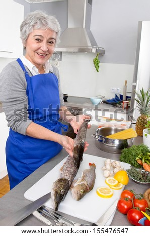 Senior woman preparing fresh fish in kitchen