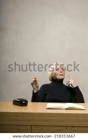 Senior woman sitting at table with book and pencil