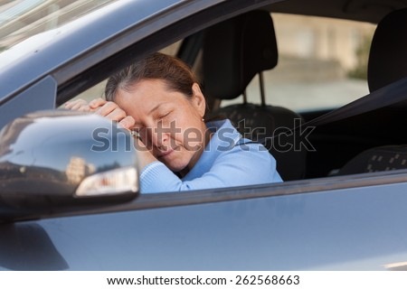 Senior woman sleeping in  black car.