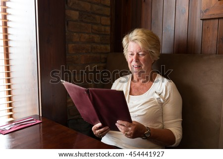 Senior woman smiling and reading a restaurant menu ready to order food