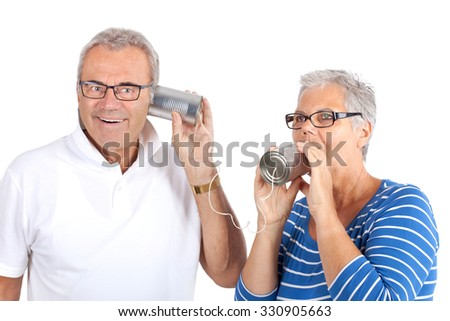 Senior woman talking through a tin can phone to her husband, isolated on white background