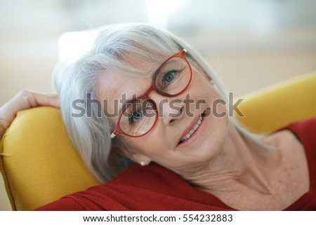 Senior woman with red sweater relaxing in armchair