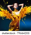 sensual attractive woman in yellow dress and paint splash - stock