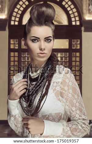 sensual brunette lady posing in fashion portrait with creative hair-style and cute make-up. Wearing sexy white lace shirt and a lot of necklaces