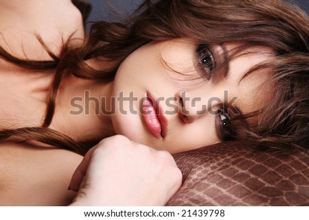 Sensual portrait of young brunette laying in a bed. Closeup.