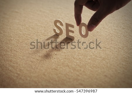 SEO wood word on compressed or corkboard with human's finger at O letter.