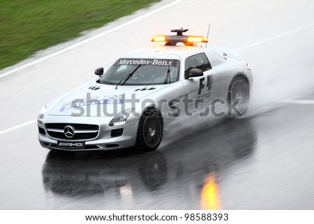 SEPANG, MALAYSIA - MARCH 25: Safety car lead the Formula One racer during heavy rain downpour in Formula One PETRONAS Malaysian Grand Prix at Sepang F1 circuit on 25 March, 2012 in Sepang, Malaysia