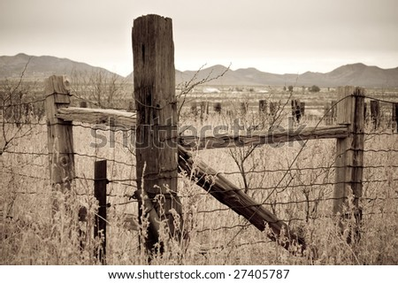 Sepia country fencepost looking over a valley in southern Arizona