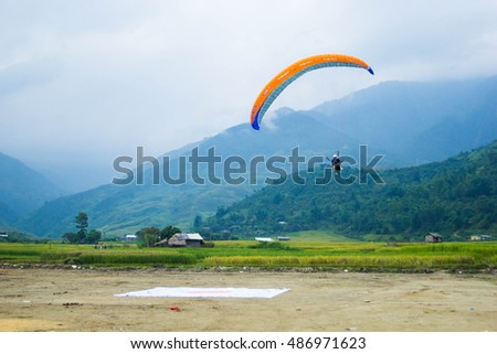 "Sept 18, 2016-The athletes parachuting are performing in Paragliding festival. ""Fly on the Golden rice season"" is an annual Paragliding festival was held at the Mu Cang Chai, Vietnam in Sept."